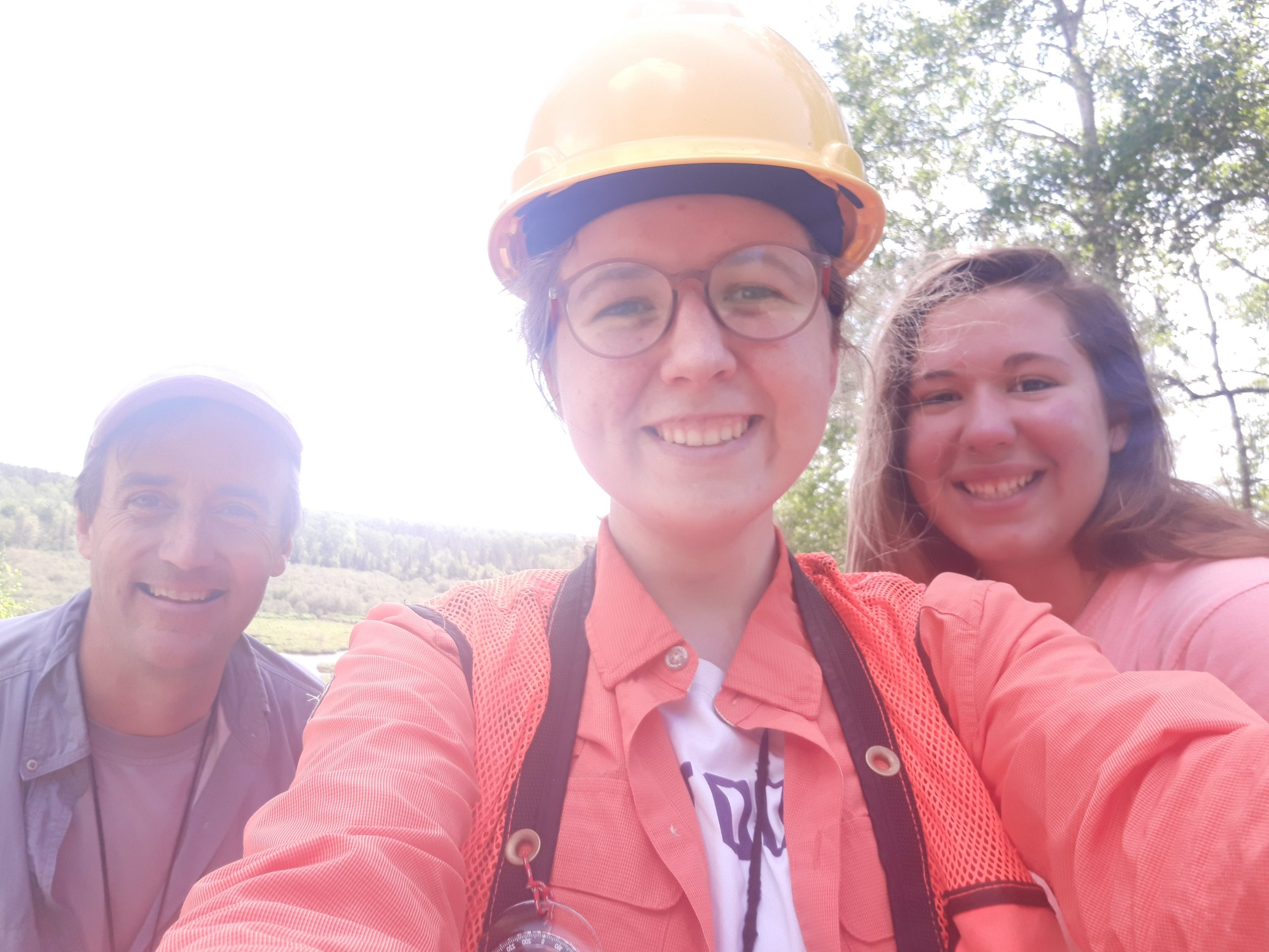 Ian, Tessa, and Emily take a selfie in the forest. Emily is wearing an orange vest and hard hat. All are smiling.