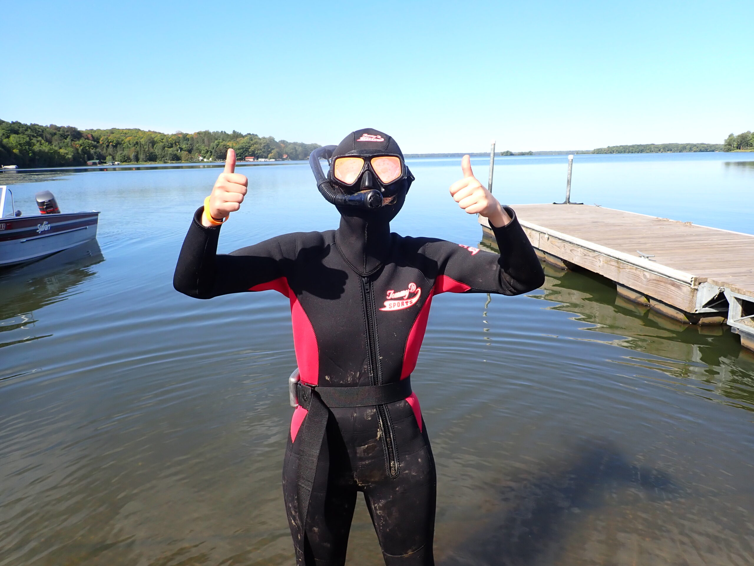 A figure in a full wetsuit with a hood and goggles stands in front of a lake giving two thumbs up.